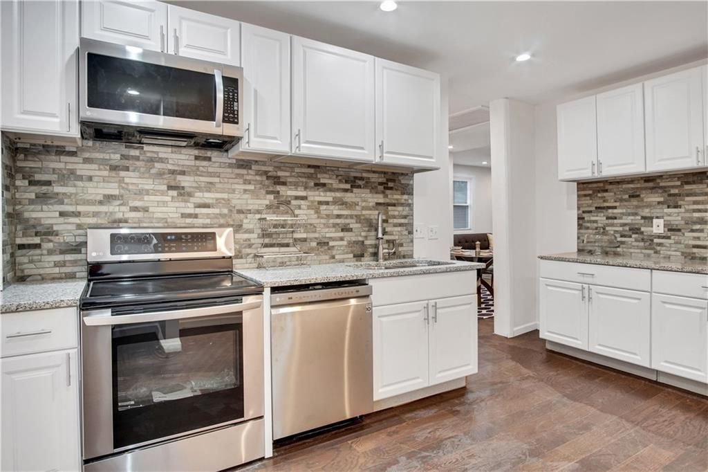 Kitchen with white cabinets, multi-colored tile backsplash, stainless appliances, and hardwood floors.