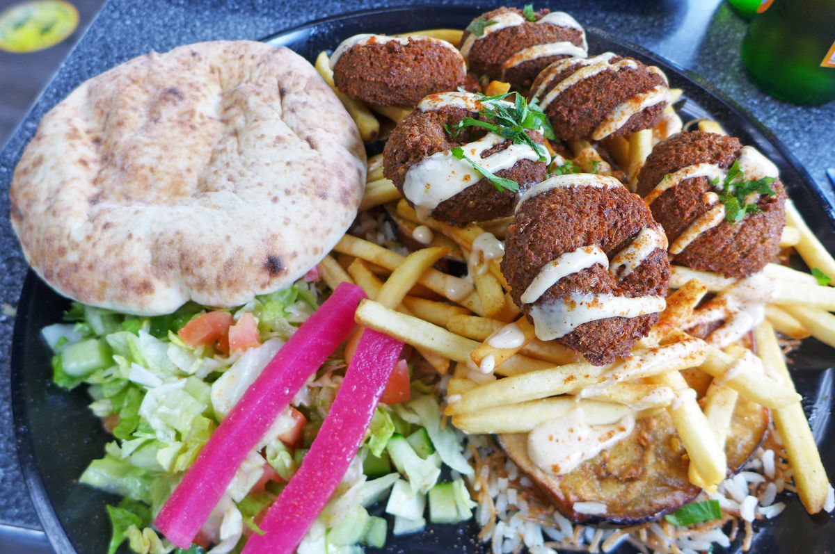 A plastic container of falafel, salad with pink sticks of beet-dyed radish, eggplant, and small round pita.