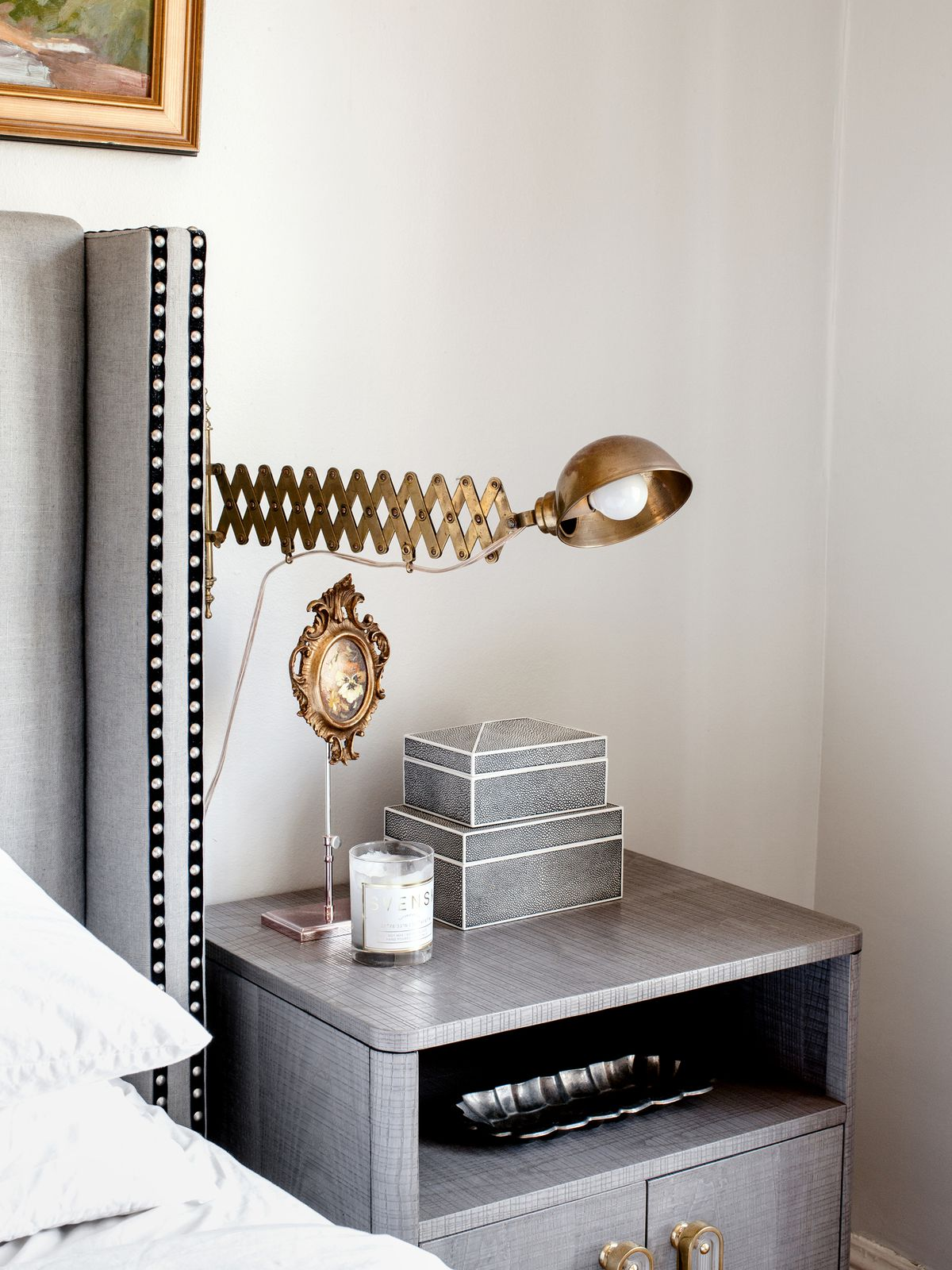 A detail shot show the corner of a headboard that is decorated with two black ribbons and nailhead trim. A brass light fixture is mounted on the wall beside it.