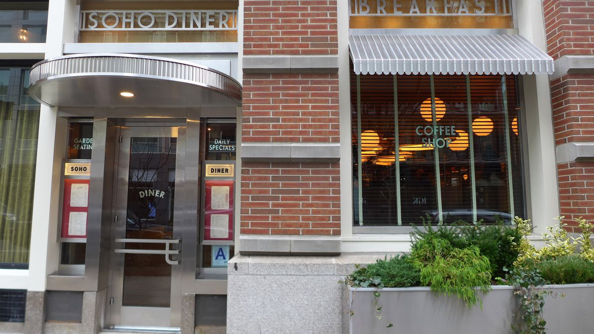 A brick facade with retro metal lettering that says Soho Diner.