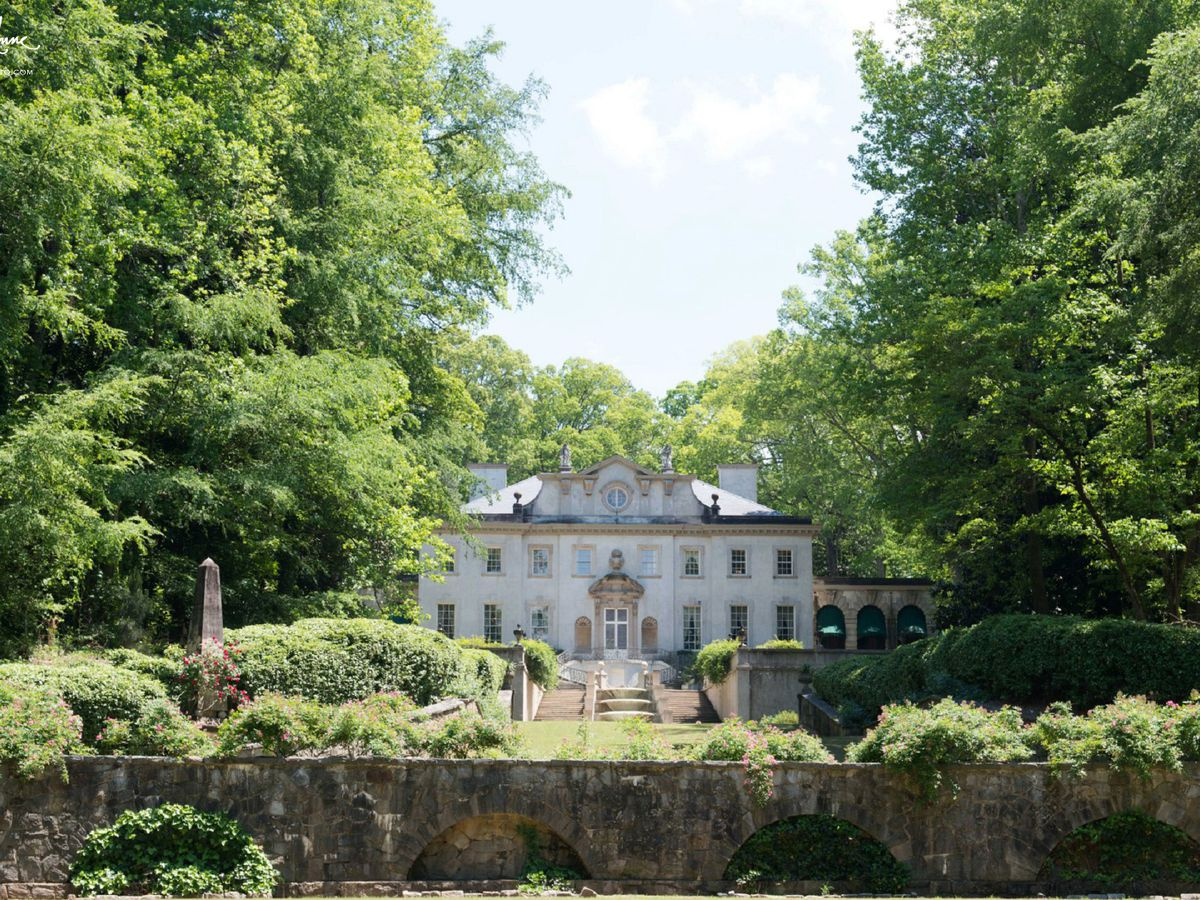 The exterior of Swan house in Atlanta. The house is white and is surrounded by trees, shrubs, and grass.