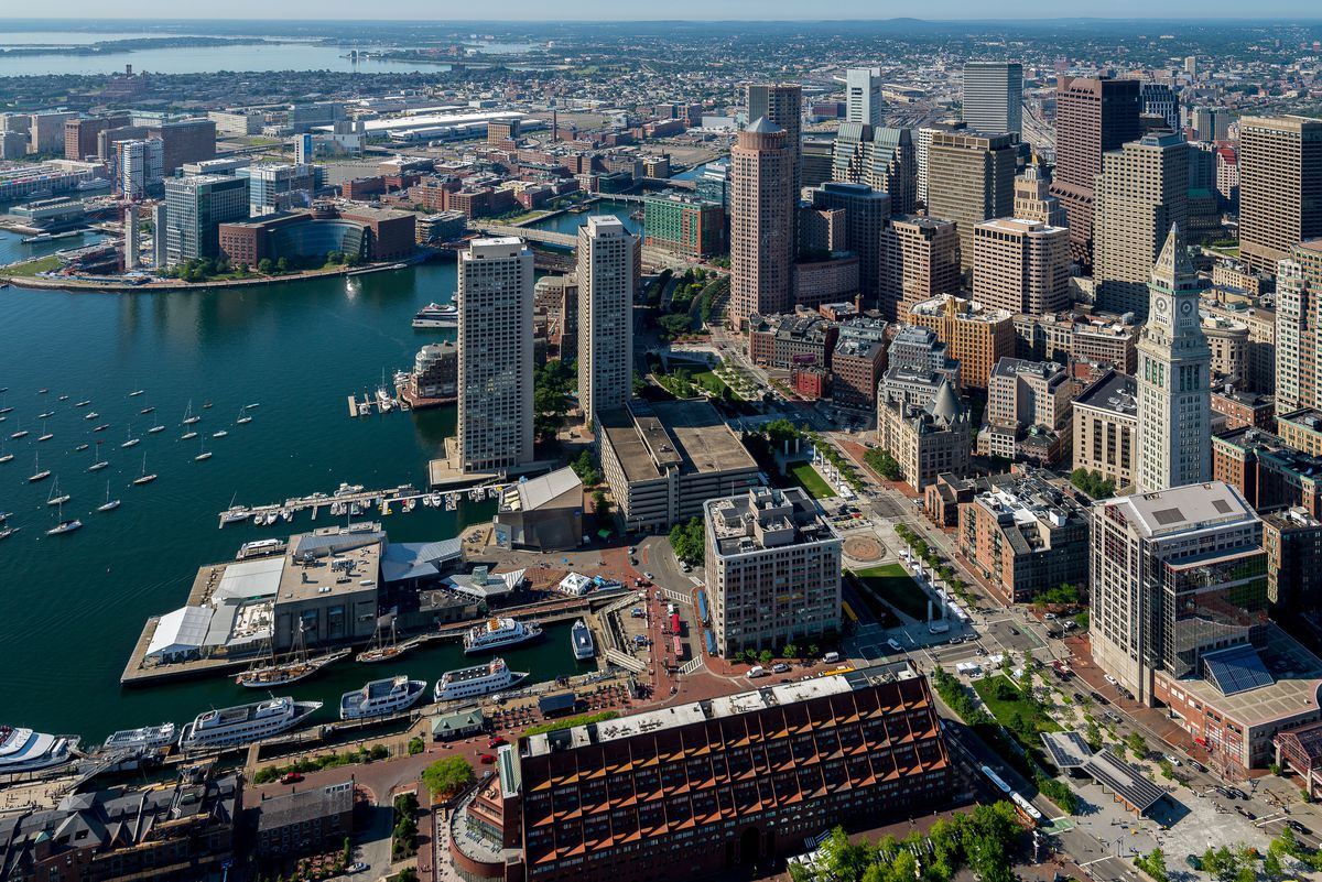 Aerial shot of a city waterfront with a big, rectangular garage next to taller buildings.