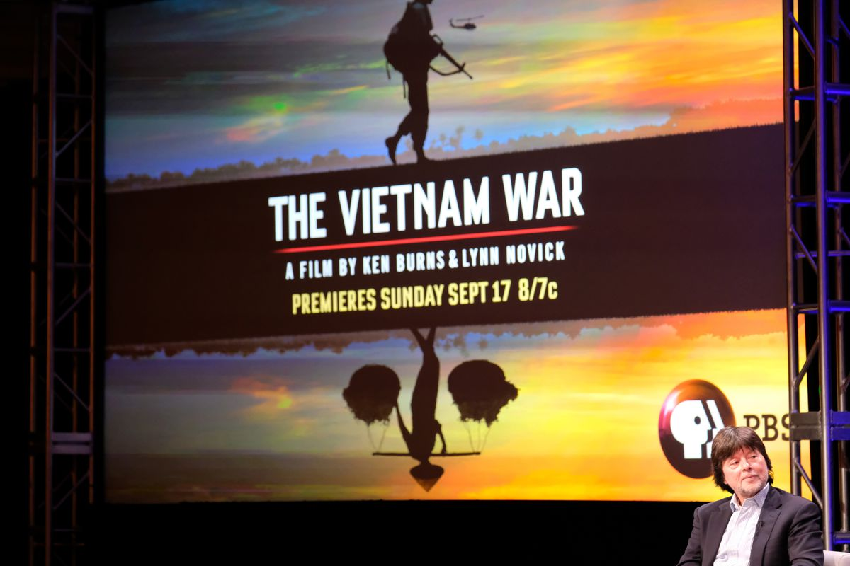 """Filmmaker Ken Burns sits onstage in front of a large screen showing a promo for his film """"The Vietnam War."""""""