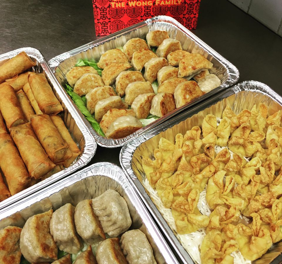 Catering trays of food, beside a restaurant menu, on a kitchen counter