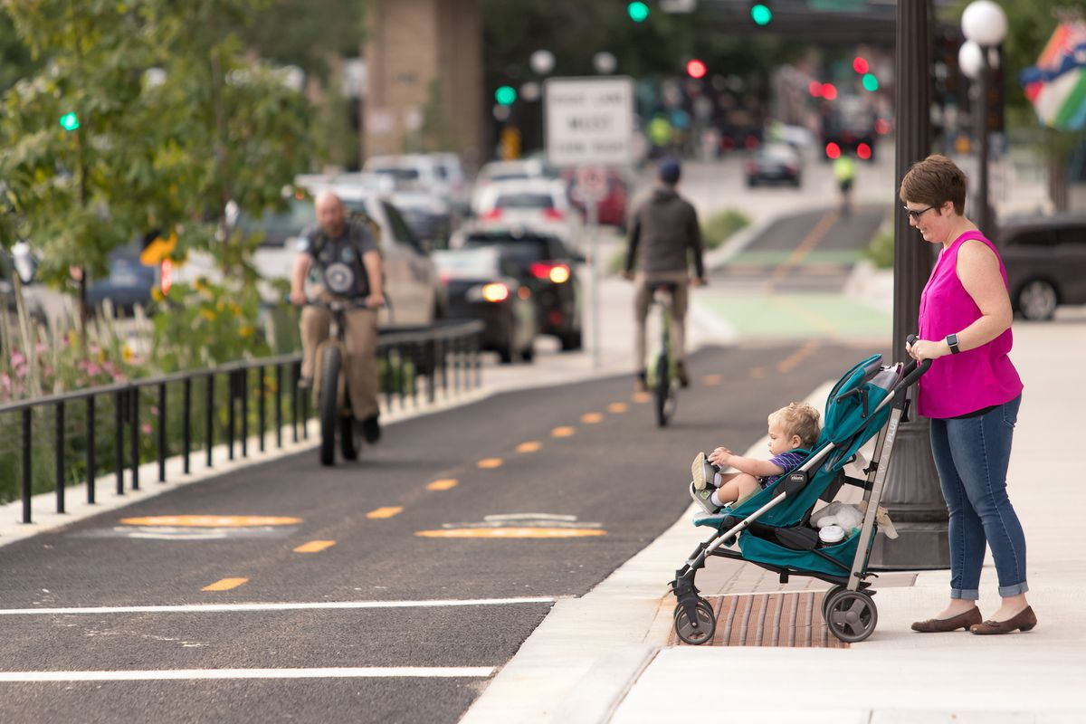 A woman with a baby in a stroller waits at a crosswalk while a man on a bike rides in a protected bike lane.