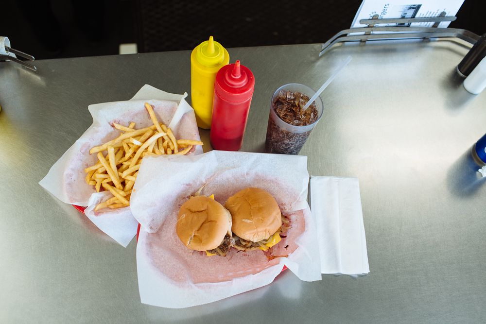 Two sliders in a basket lined with wax paper on a metal counter next to a basket of fries on wax paper and yellow mustard and red ketchup bottles. There's also a plastic cup filled with brown soda and ice.