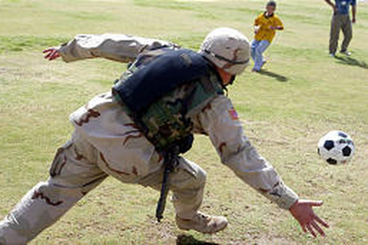 Cpt. John Poole, 28, of Los Angeles, from the 4th Infantry Division in Tikrit, Iraq, plays soccer with a small local boy Saturday. The 1st Brigade has started a youth program.