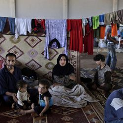 In this Thursday, Sept. 13, 2012, photo, a Syrian family, who fled their home due to government shelling, take refuge at Bab Al-Salameh crossing border, hoping to cross to one of the refugee camps in Turkey, near the Syrian town of Azaz. The days are still hot across the fertile plains of northern Syria, but at night there is a hint of a chill an ominous harbinger of winter's approach and the deepening of the humanitarian crisis gripping a country wracked by civil war.