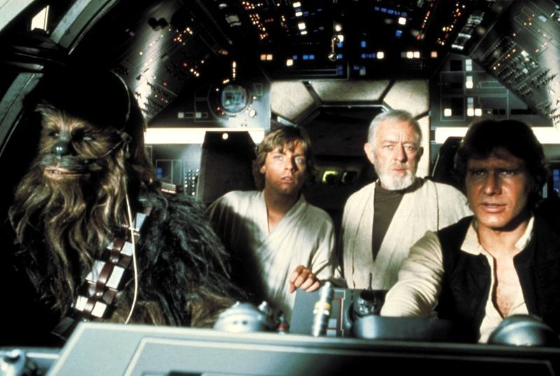 Chewie and Han Solo piloting the Millennium Falcon — with Luke Skywalker and Obi-Wan Kenobi as passengers — in the original 1977 Star Wars film.