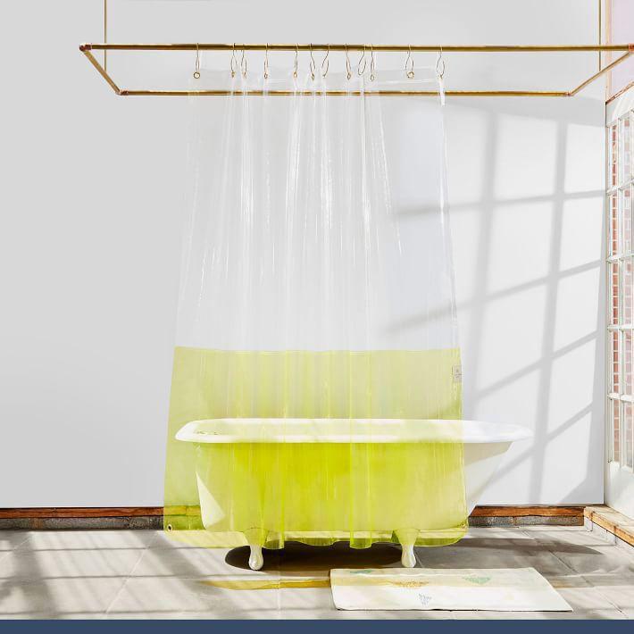 Freestanding bathtub with clear curtain.