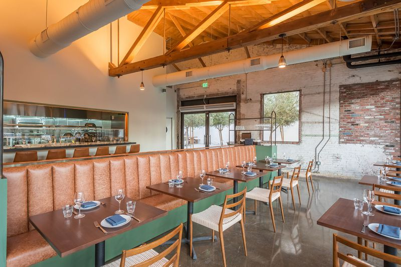 A warehouse-like dining room with open ceiling and leather banquettes.