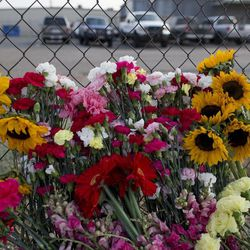 Flowers sit against the fence outside the Granite Mountain Hot Shot Crew fire station, Monday, July 1, 2013, in Prescott, Ariz. An out-of-control blaze overtook the elite group of firefighters trained to battle the fiercest wildfires, killing 19 members as they tried to protect themselves from the flames under fire-resistant shields. The disaster Sunday afternoon all but wiped out the 20-member Hotshot fire crew leaving the city's fire department reeling. (AP Photo/Julie Jacobson)