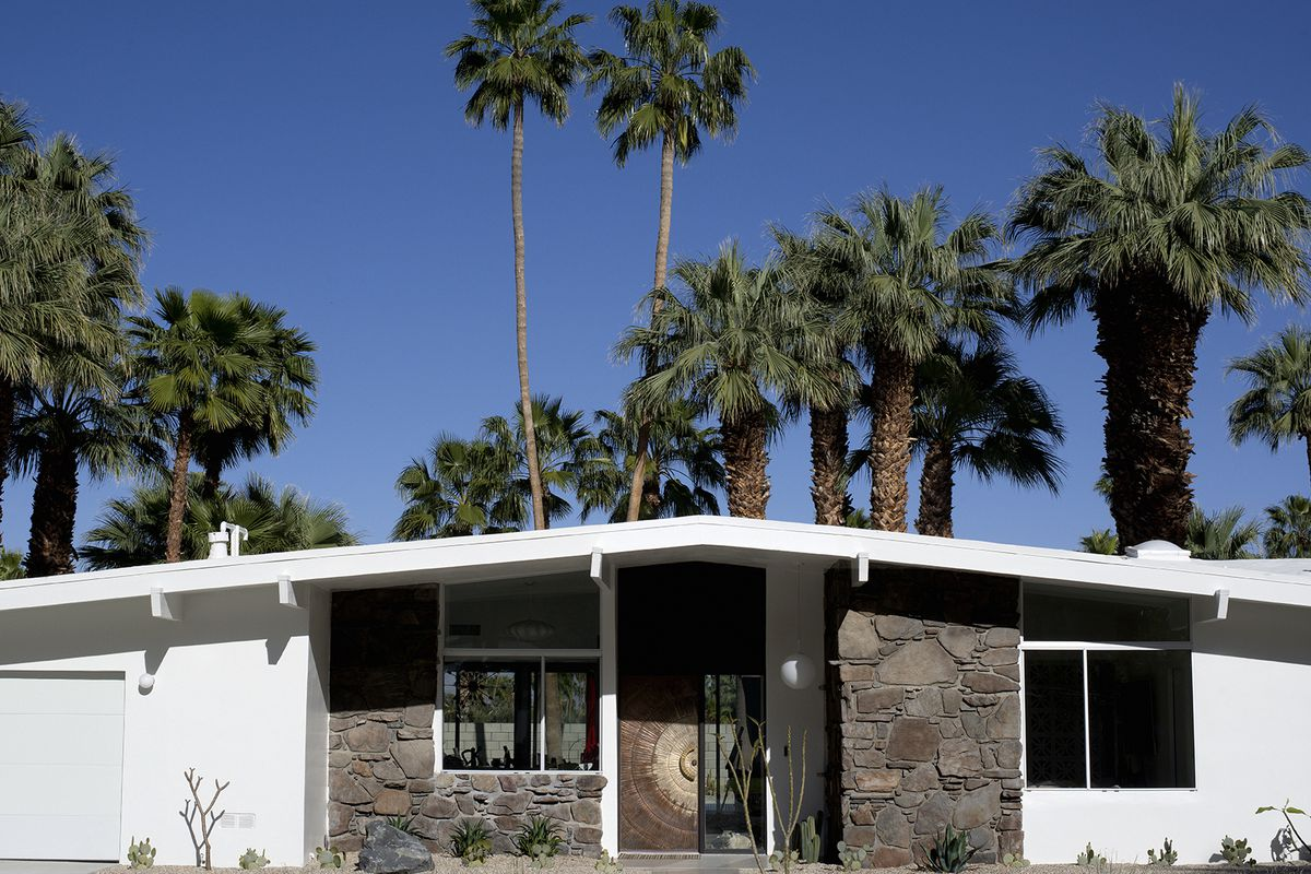 Broadly gabled white roof over single-story home with white timber and stone facade with palm trees in the background.