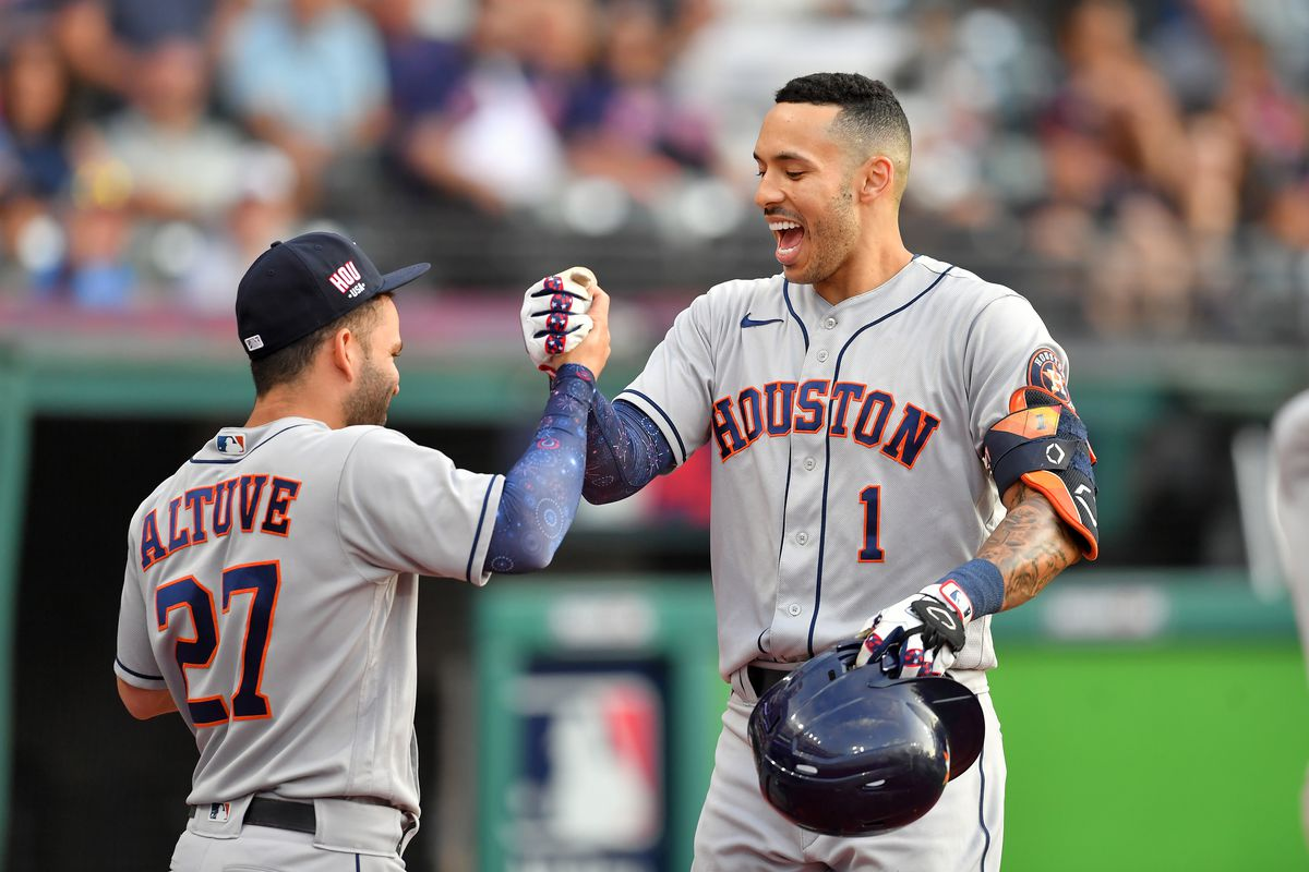 Jose Altuve celebrates with Carlos Correa of the Houston Astros after Correa hit a solo homer during the fourth inning against the Cleveland Indians at Progressive Field on July 03, 2021 in Cleveland, Ohio.