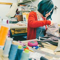 A seamstress sews lining inside a Thom Browne blazer.