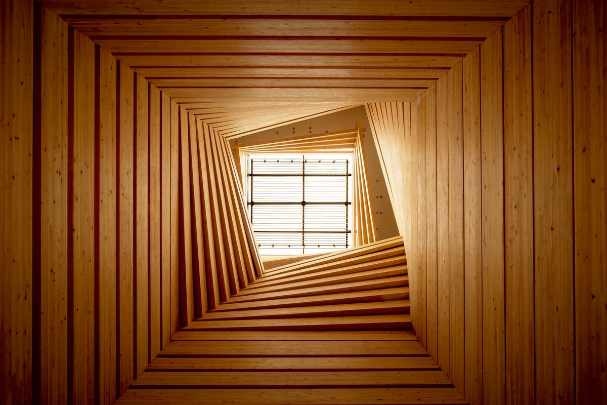 A view up the tImber atrium shows stacks of twisted wood culminating in a skylight.