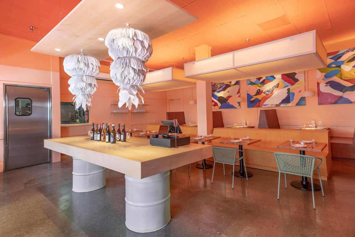 Orange walls and hanging paper sculptures inside of a new restaurant dining room.