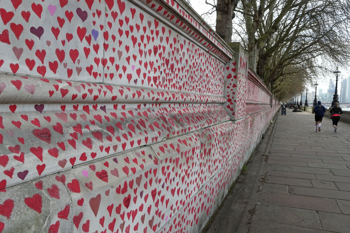 People jog past the 'The National COVID Memorial Wall' on the south bank of the Thames in front of St. Thomas' hospital and opposite the House of Parliament in London, Sunday April 4, 2021. Hearts are being drawn onto the wall in memory of the many thousands of people who have died in the UK from coronavirus, with organizers hoping to reach their target of 150,000 hearts by the middle of next week.