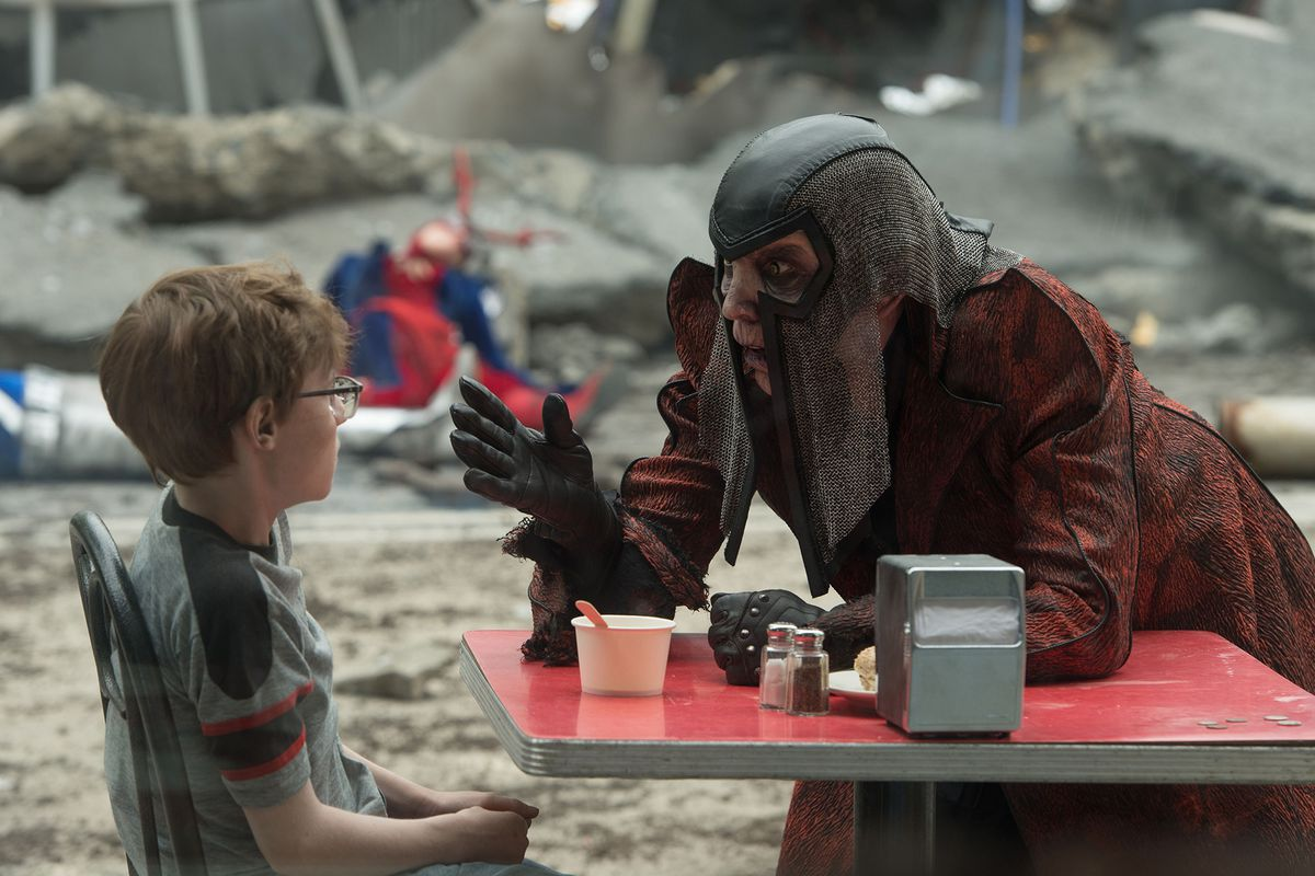 The Terror, a very old man with a long red coat and a chainmail mask, talks to a young boy sitting at a table