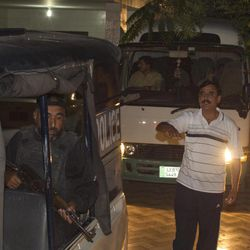 Police officers escort a vehicle  carrying the family of Osama bin Laden, in Islamabad, Pakistan on Thursday, April 26, 2012. A minivan carrying the three widows and children of Bin Laden has left the house where they have been staying in Islamabad and is en route to the airport, from where they will be deported to Saudi Arabia, officials and witness said.