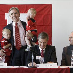 University of Utah President Michael Young holds his grandchildren Trevor, left, and Bryce Owen as he states that the U.'s move to join the Pac-10 is a decision that will affect future students like his grandchildren at the Rice-Eccles Stadium Thursday. Seated are University of Utah athletic director Chris Hill, center, and Pac-10 Commissioner Larry Scott.