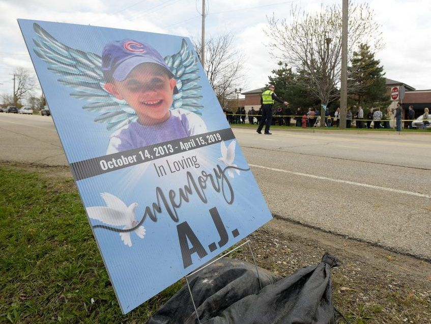 Signs and ribbons line the street in front of the Davenport Family Funeral Home, where the visitation of 5-year-old AJ Freund of Crystal Lake was held last week in Crystal Lake. | Mark Black/For the Sun-Times