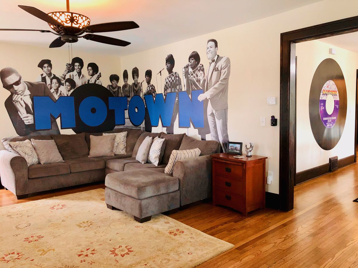 """A gray sectional couch right below a big """"Motown"""" mural. A large vinyl painting is on the wall of the next room."""