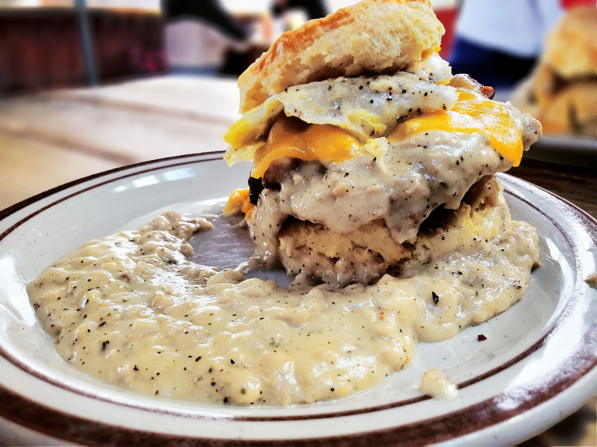 A fried chicken biscuit sandwich is seen on a plate surrounded by off-white sausage gravy