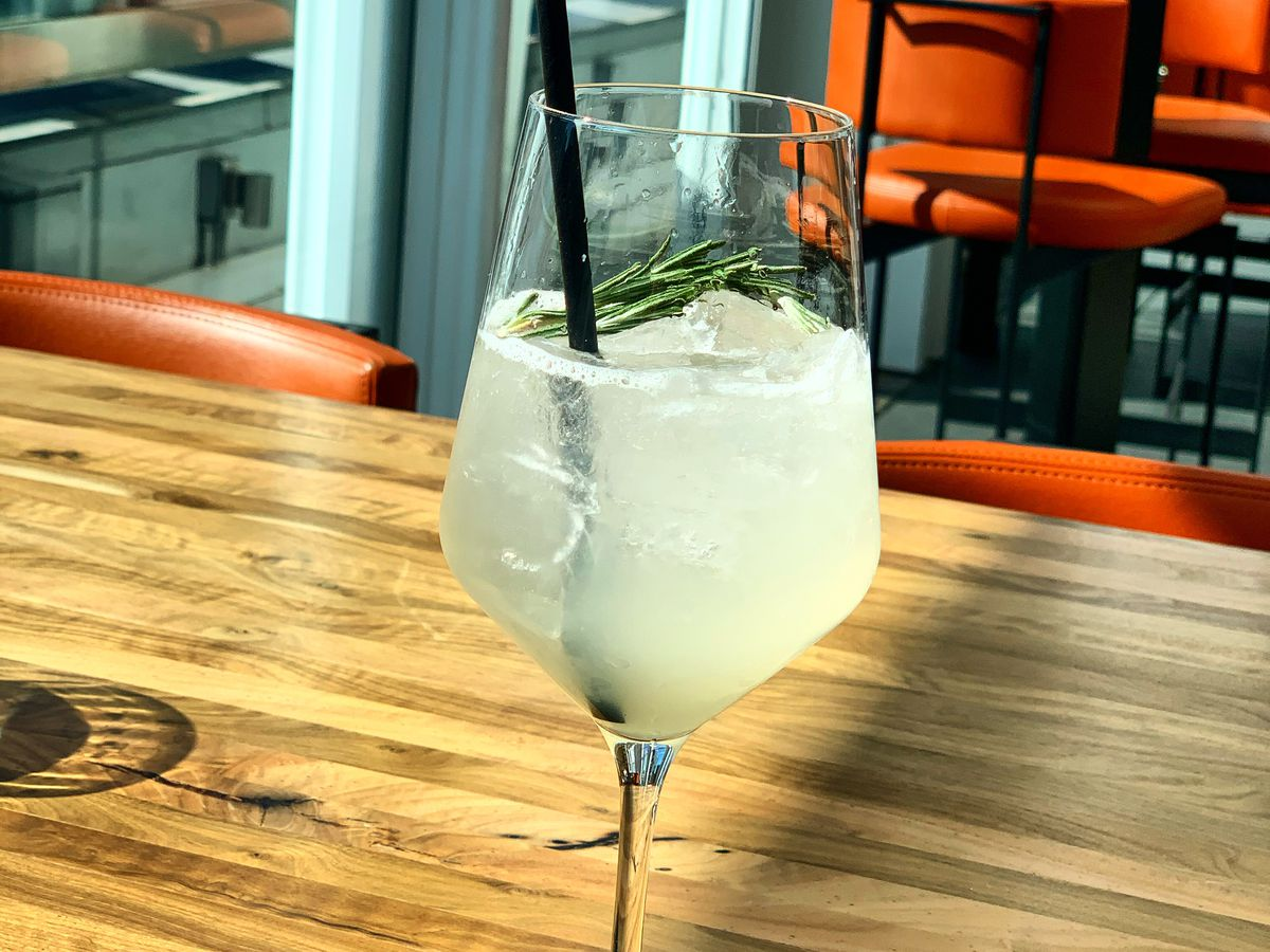 A light yellow cocktail sits in a wine glass, topped with a rosemary sprig.