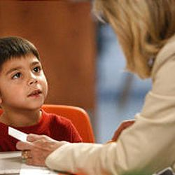 First-grader Isaiah Romero works with Brenda Shockey at the Guadalupe Schools. Reading tutors work one-on-one with the children.