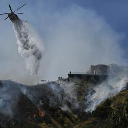 A helicopter makes a water drop next to a home in Burbank, Calif., Wednesday, June 28, 2017. Dozens of homes were under mandatory evacuation orders on the suburban edges of Burbank, where flames raced uphill through tinder-dry grass.