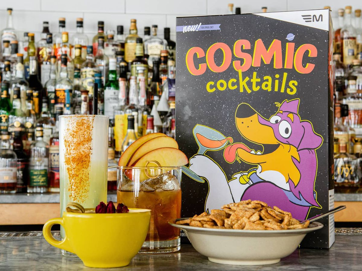 A quirky-branded box of cereal, with a bowl of cereal and several cocktails on a bartop