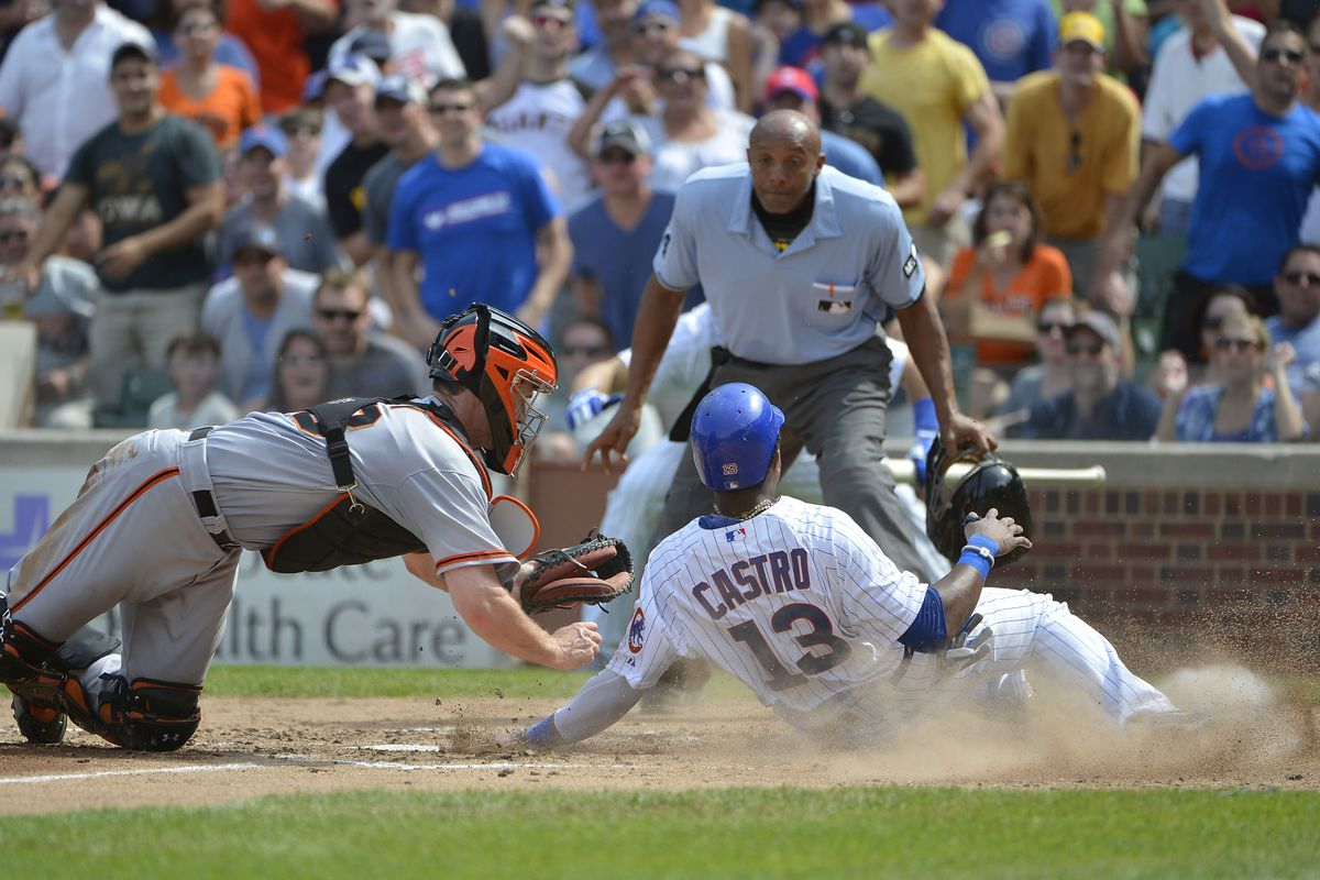 Starlin Castro of the Chicago Cubs scores past catcher Buster Posey of the San Francisco Giants at Wrigley Field in Chicago, Illinois.  (Photo by Brian Kersey/Getty Images)