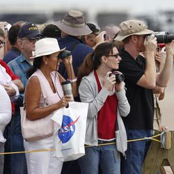 A large crowd strains for a good look of Space Shuttle Endeavour as it prepares to land atop NASA's 747 Shuttle Carrier Aircraft at Ellington Field in Houston on Wednesday, Sept. 19, 2012. Endeavour will spend the night in Houston before continuing its journey from the Kennedy Space Center in Florida to the California Science Center in Los Angeles where it will be on permanent display.