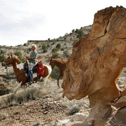 Dean Bradshaw, complete with a foam pad on his saddle, rides past a rock formation in the Sid's Mountain Wilderness Study Area. The landscape of the Swell defies description.
