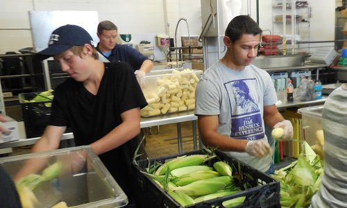 Baseball players from Greeley West High School shucked corn on a recent afternoon as part of the team's fundraising effort.