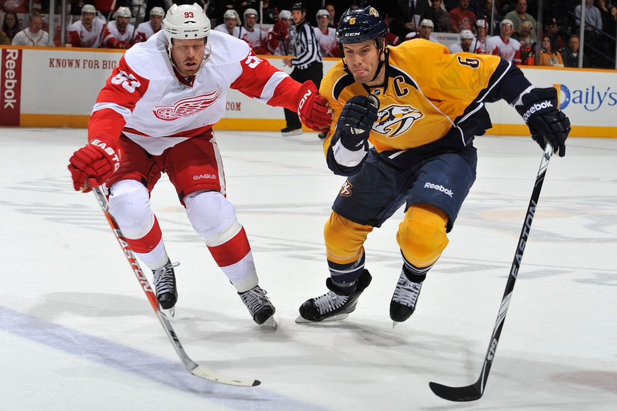 NASHVILLE, TN - DECEMBER 15:  Johan Franzen #93 of the Detroit Red Wings races Shea Weber #6 of the Nashville Predators for the puck at the Bridgestone Arena on December 15, 2011 in Nashville, Tennessee.  (Photo by Frederick Breedon/Getty Images)