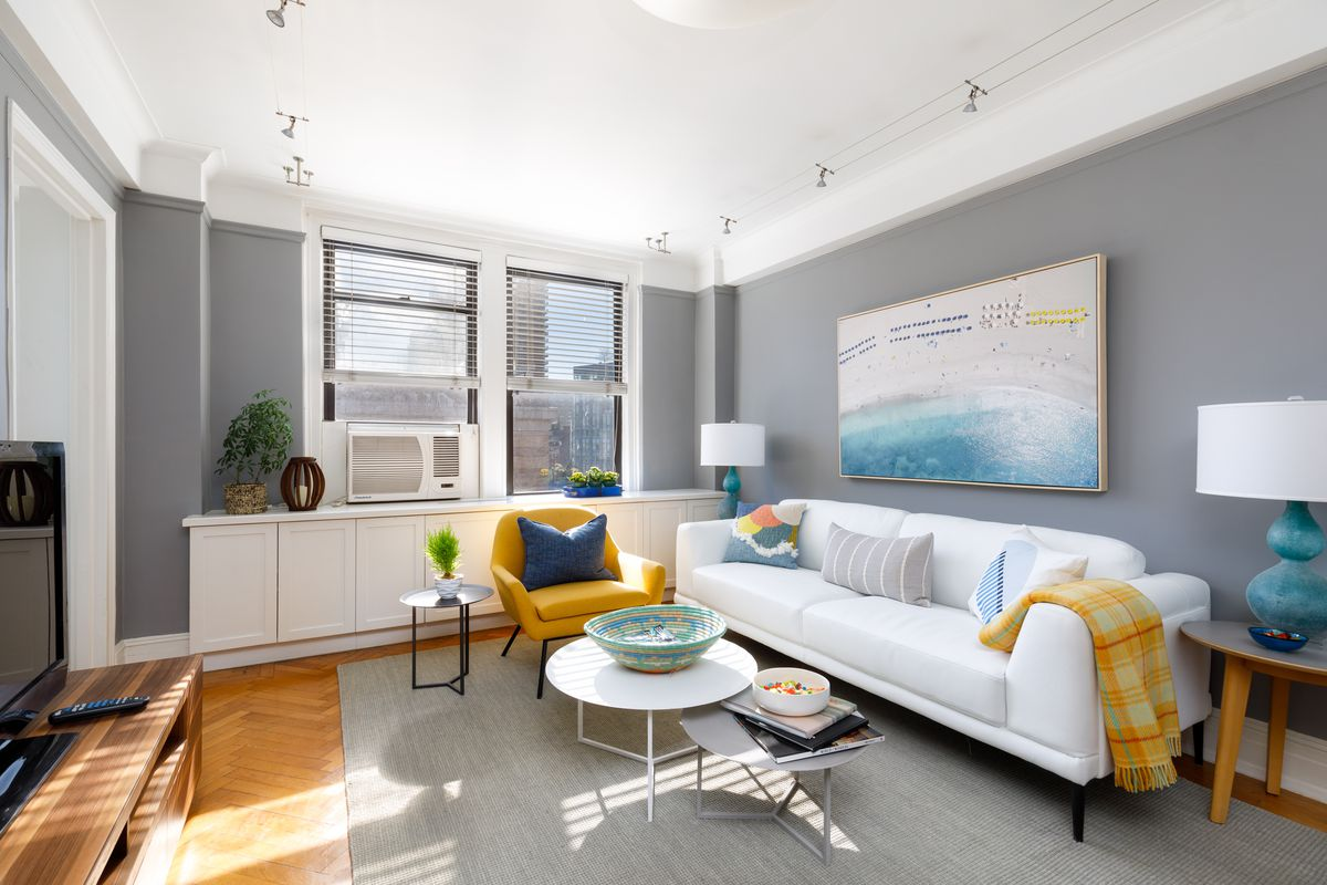 A living room with a grey rug, grey walls, two windows, and a white couch.