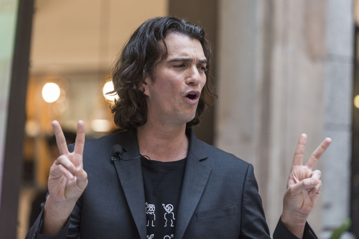 WeWork CEO Adam Neumann holds up both hands in V-for-victory signs.