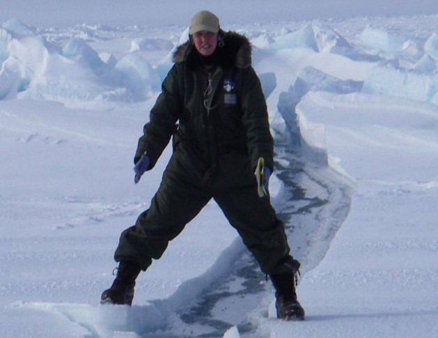 Arctic researcher Cathy Geiger, 200 miles north of Barrow, Alaska, straddling a fissure in the ice and snow.