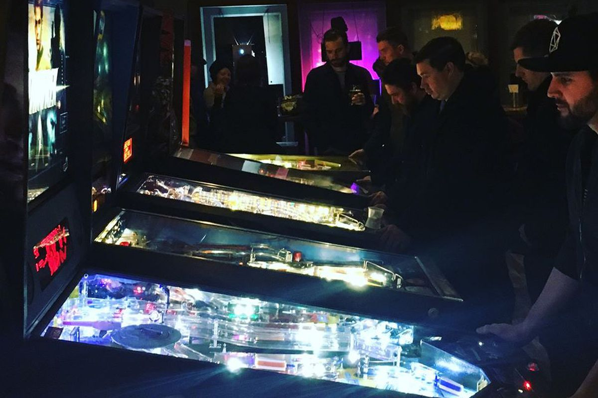 In a dark room, a line of lit up pinball machines with players