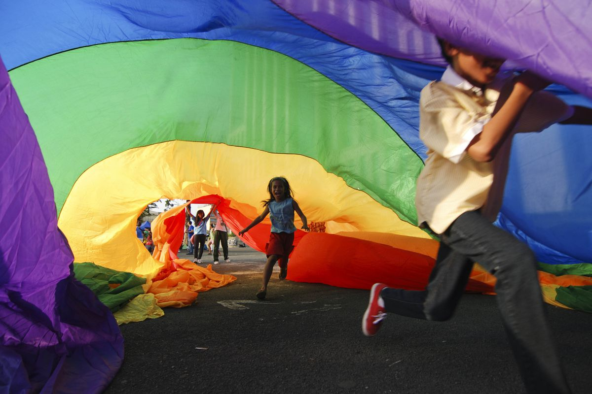 Children play under a rainbow flag at the Manila Gay Pride March in the Phillippines.