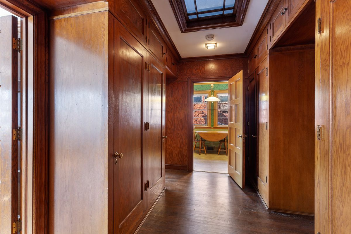 A hallway full of storage cabinets and a skylight.