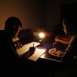 Marlon Alfafara, left, is an LDS Ward Mission Leader. He lost his home during the typhoon in Tacloban, Thursday, Nov. 21, 2013. Here, he works on a list of members by candlelight. At right is Ronaldo Rosaldo who also lost his home.