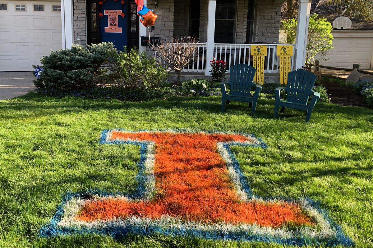 """A giant orange """"I"""" painted on a lawn of a suburban house signals that someone living there will be attending the University of Illinois."""