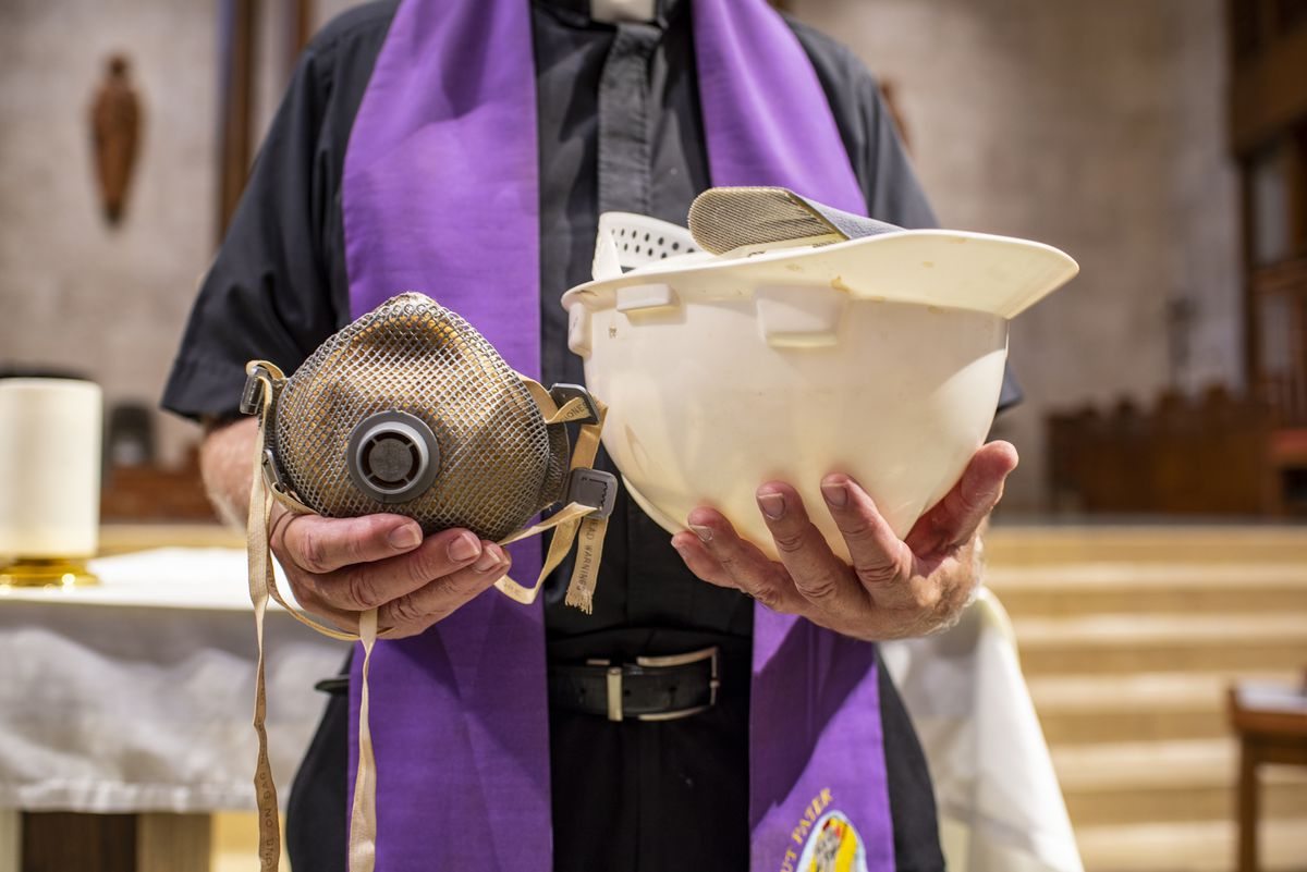 """Father Bruce Nieli holds the mask and helmet he wore at New York's ground zero at St. Austin Catholic Parish in Austin, Texas, on Thursday, Sept. 9, 2021. Father Nieli was at ground zero shortly after the Sept. 11 attacks when officials made the largest discovery of bodies since the attack. Through his experience, Father Nieli came to better develop a """"spirit of reconciliation and peace."""""""