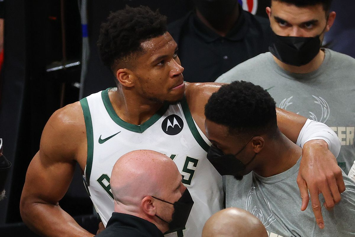 Giannis Antetokounmpo of the Milwaukee Bucks is helped off the court after being injured on a play against the Atlanta Hawks during the second half in Game Four of the Eastern Conference Finals at State Farm Arena on June 29, 2021 in Atlanta, Georgia.