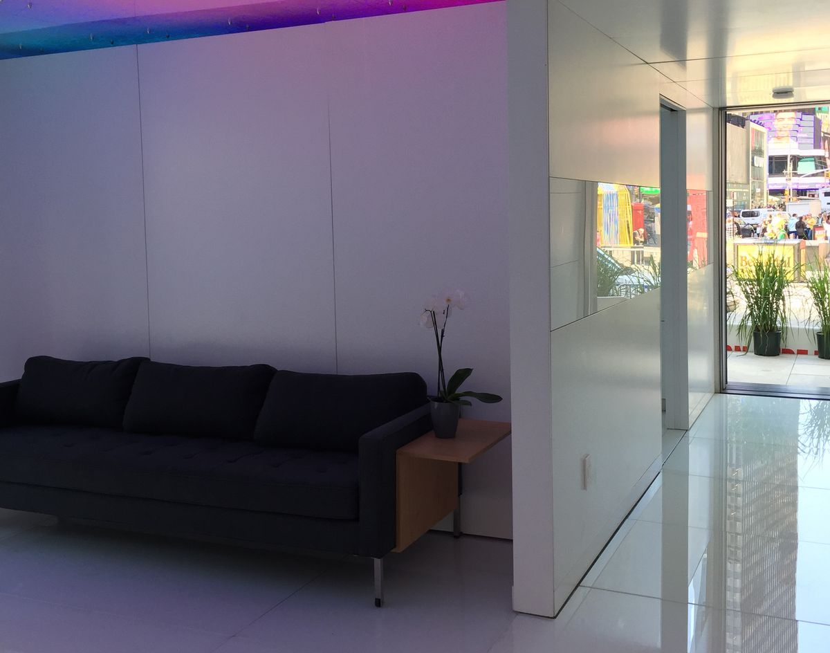 The interior of Futurehaus in Times Square. The walls and floors are white and lit with colorful smart lighting.