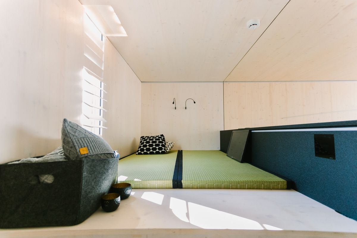 A bedroom area. The bed is a green cushion that sits on the floor. There are two thin black light fixtures above the bed.