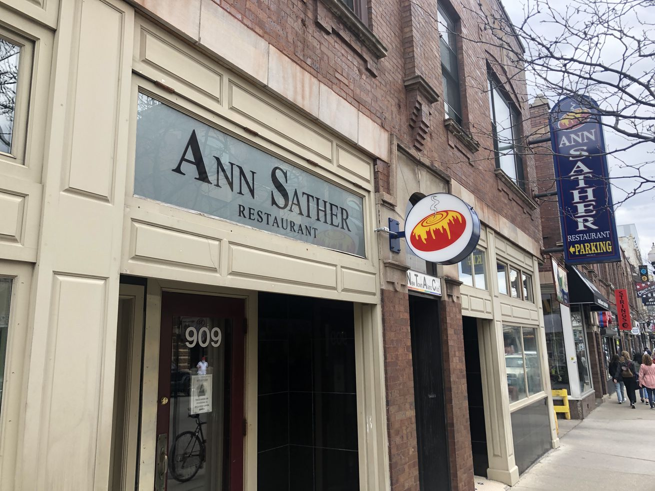 """The exterior signage of a restaurant """"Ann Sather"""" on a sidewalk."""